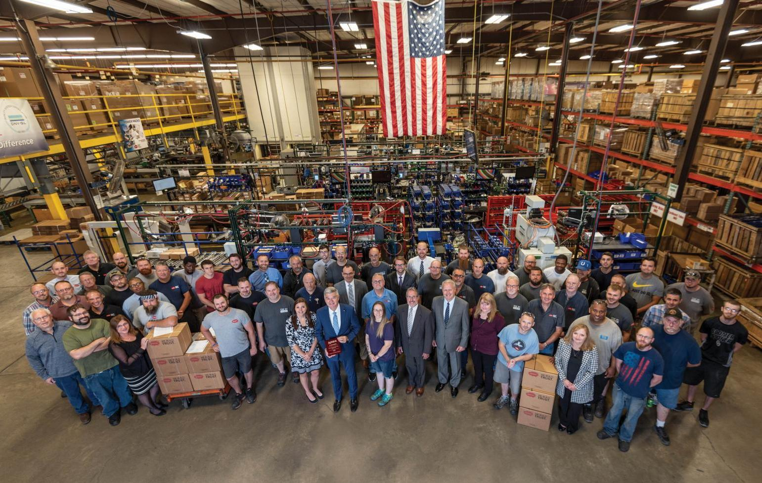 Muncie Power Products employees gather as they present the NTEA 55-year membership plaque.