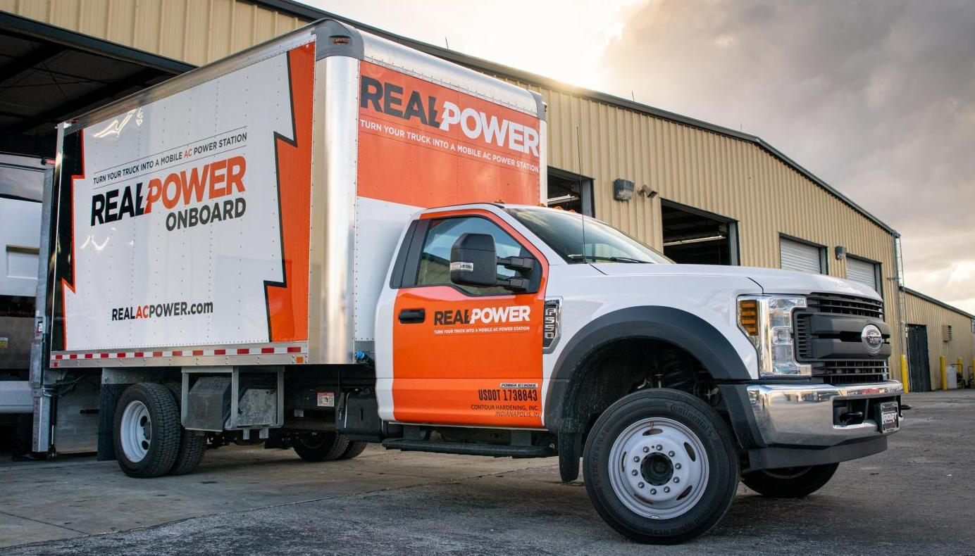 Real Power truck in front of a garage